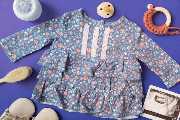 Vestido de bebé rodeado de biberón; chupete; cepillo; zapatos y imagen de ultrasonido sobre fondo azul.