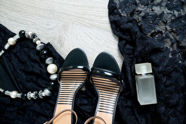 Vestido de encaje negro, sandalias, collar y perfume.