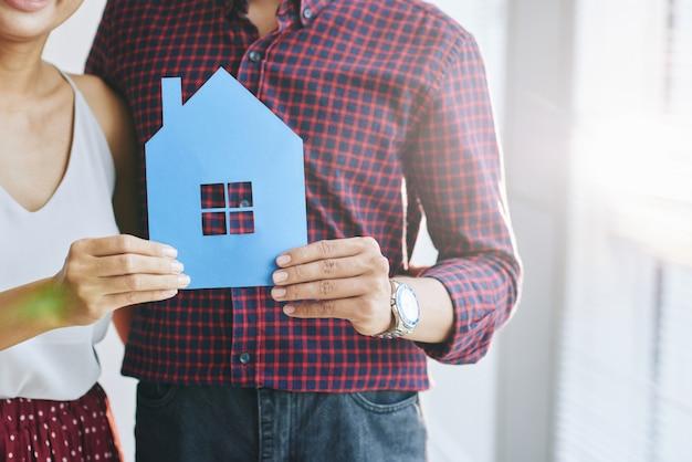 Vestido informalmente irreconocible pareja abrazándose y posando con recorte de papel de la casa
