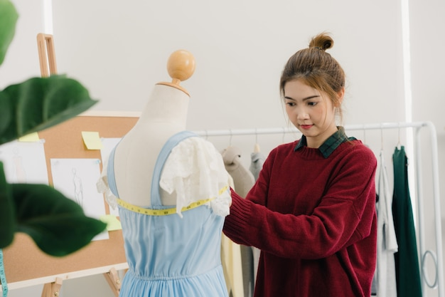 Vestido de medición de trabajo del diseñador de moda de sexo femenino asiático hermoso profesional en una ropa del maniquí