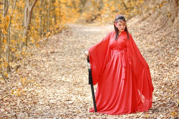 Vestido de mujer asiática hermosa joven en estilo tradicional chino antiguo guerrero de moda con antigua palabra y paraguas. mujer linda en el vestido rojo que se coloca y que mira lejos al aire libre.