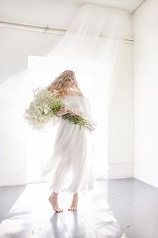 Vestido de niña de luz blanca y pelo rizado con flores.