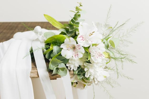 Vestido de novia blanco y ramo de jazmín auriculatum sobre tabla de madera.