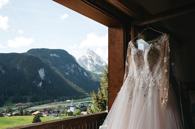 Vestido de novia cuelga de una percha en una ventana con vista a las montañas
