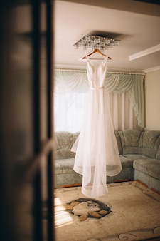 Vestido de novia de novia colgado en la habitación.