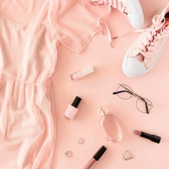 Vestido plano de mujer, zapatillas, cosméticos y accesorios sobre un fondo rosa pastel.