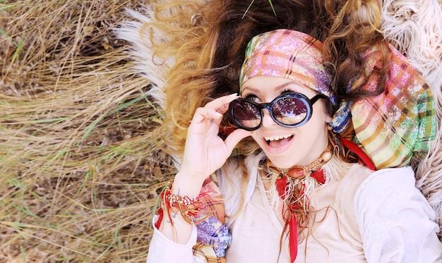 Vestido con retrato de mujer de estilo boho chic acostado en un heno y piel, saludable y feliz
