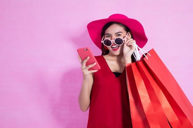 Vestido rojo de la muchacha bonita asiática feliz que sostiene los panieres y el teléfono elegante que miran lejos en fondo rosado