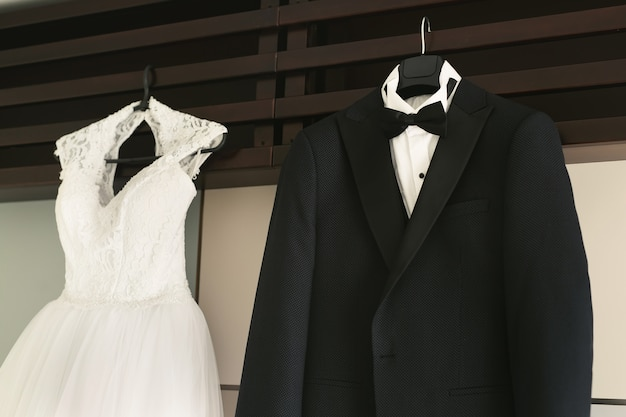 El vestido del traje de la novia y el novio cuelga de una percha