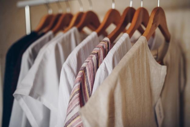 Los vestidos confeccionados de tonos claros cuelgan de perchas.