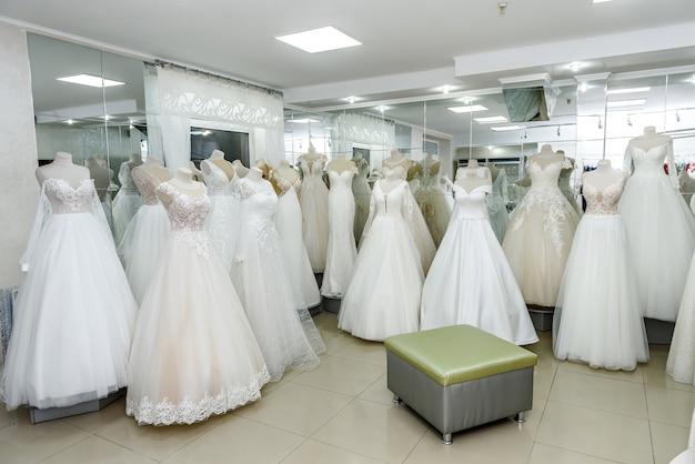 Vestidos de novia de moda en percha y maniquíes en salón
