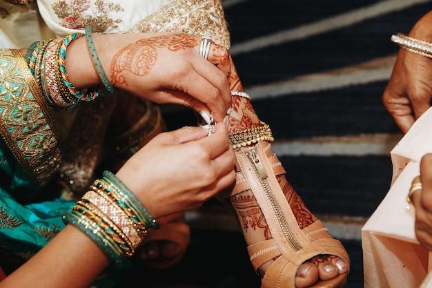 Vestir zapatos para la novia india antes de la boda