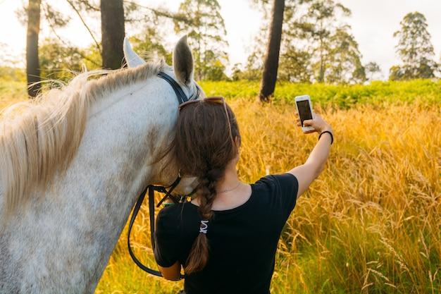 Veterinario femenino tomando selfie con caballo en puesta de sol