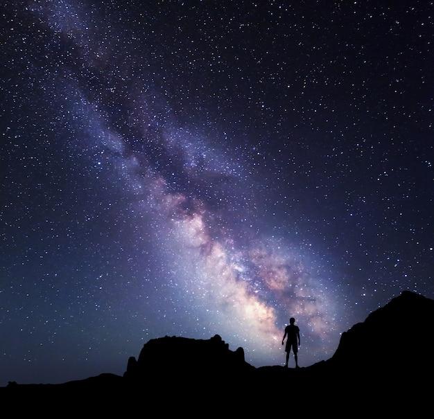 Vía láctea en el cielo nocturno y la silueta de un hombre de pie