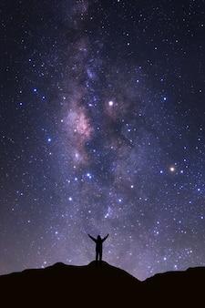 Vía láctea galaxia y silueta de un hombre feliz de pie