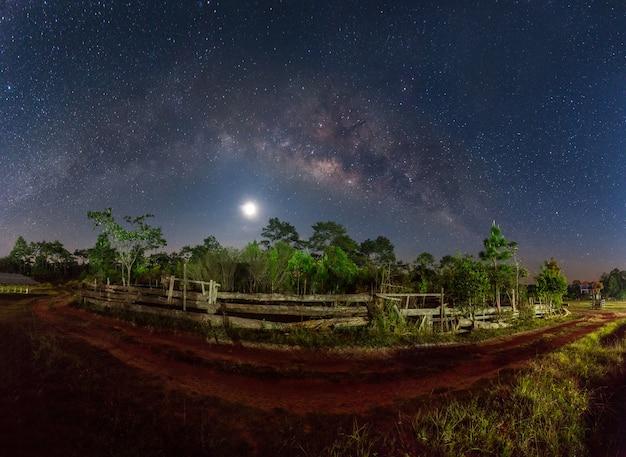 Vía láctea y luna llena sobre camino de tierra en campo