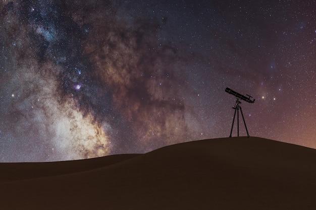 Vía láctea con pequeño telescopio en el desierto.