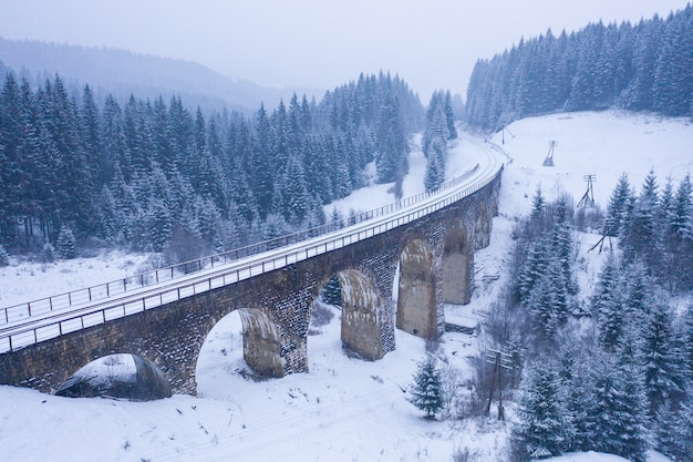 Viaducto nevado viejo. antiguo puente ferroviario cubierto de nieve en ucrania