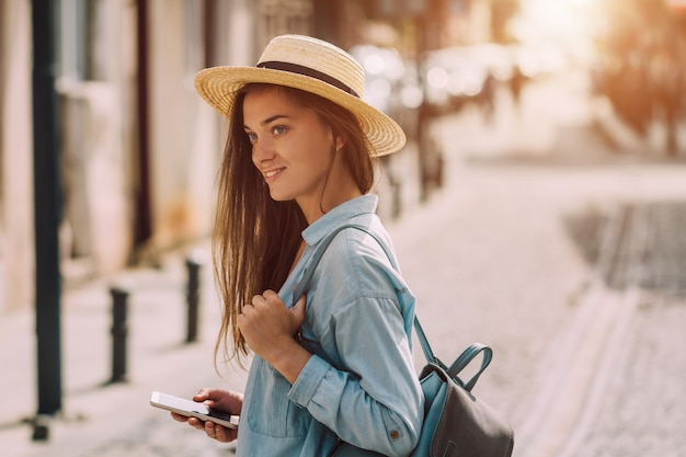 Viaja mujer con sombrero con mochila y teléfono caminando por la calle de una ciudad europea. vacaciones y estilo de vida de viaje