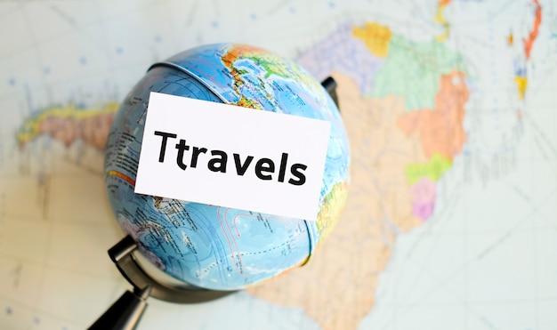 Viaja texto en una hoja blanca con globo en la superficie del mapa del atlas