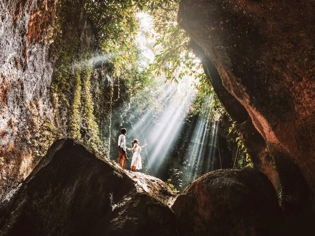 Viajando joven pareja con rocas de la selva tropical en bali