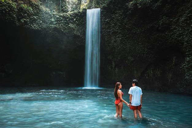 Viajando joven pareja con selva tropical en bali disfrutando de la vida en la hermosa cascada de tibumana.