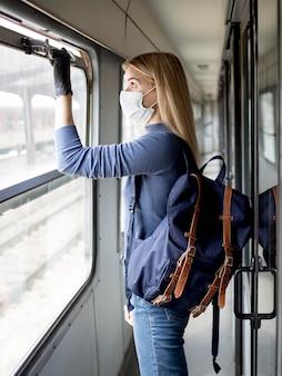 Viajando mujer en tren con máscara