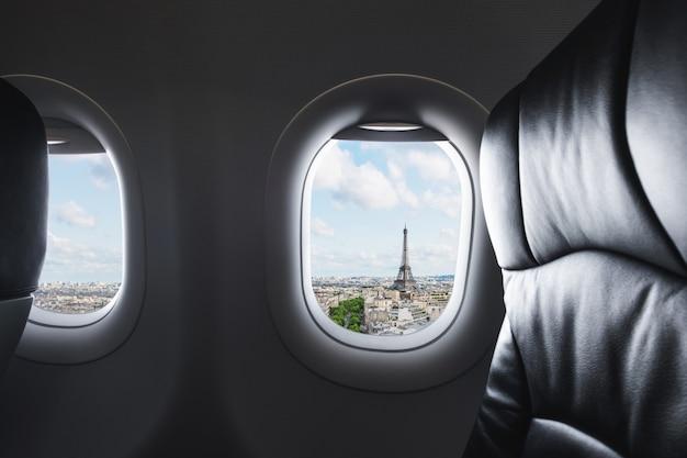 Viajando a parís, francia, famoso punto de referencia y destino de viaje en europa. vista aérea de la torre eiffel a través de la ventana del avión.