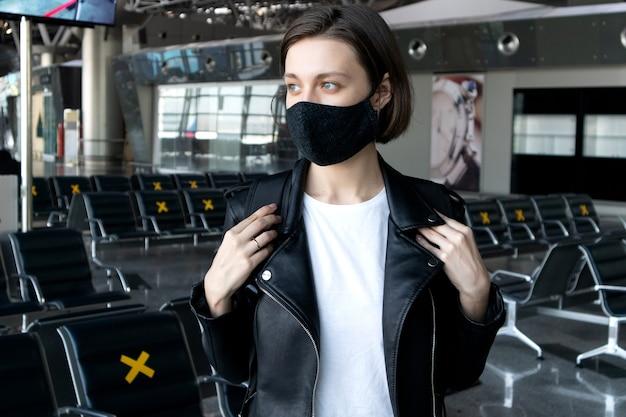 Viajar en avión durante la pandemia de coronavirus. mujer joven con mascarilla en el aeropuerto internacional.