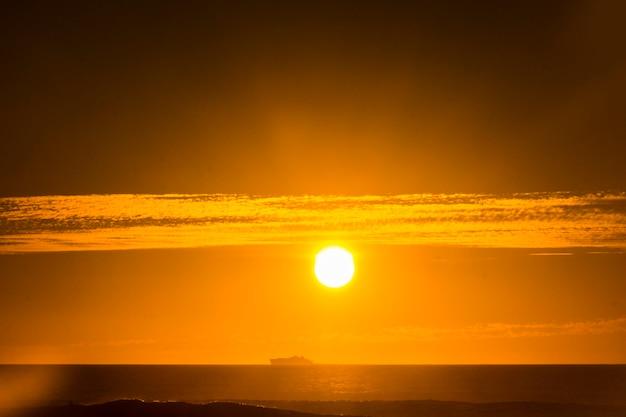 Viajar en barco de crucero por concepto de vacaciones con horizonte y gran sol naranja en backgorund