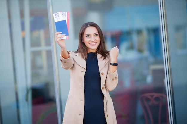 Viajar. mujer joven alegre que sostiene boletos de avión al aire libre