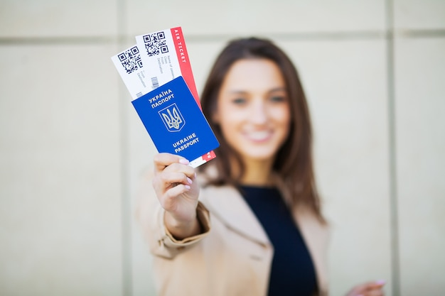 Viajar. mujer sosteniendo dos pasajes aéreos en el pasaporte extranjero cerca del aeropuerto