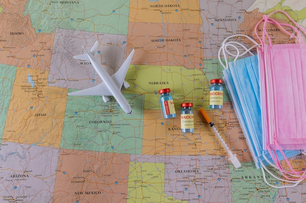Viajar durante la pandemia del covid-19. modelo de avión, máscara médica de protección, botella de vacuna, jeringa con mapa de américa del norte