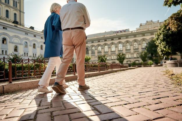 Viajar pareja de ancianos con estilo caminando juntos al aire libre