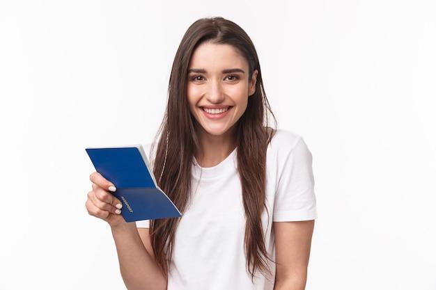 Viajar, vacaciones, concepto de verano. retrato de primer plano de linda y feliz mujer joven en camiseta, sosteniendo el pasaporte abierto y sonriendo