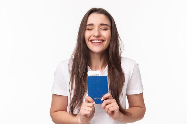 Viajar, vacaciones, concepto de verano. retrato de primer plano de una niña feliz y soñadora que se siente feliz finalmente viaja, con pasaporte con boleto de avión