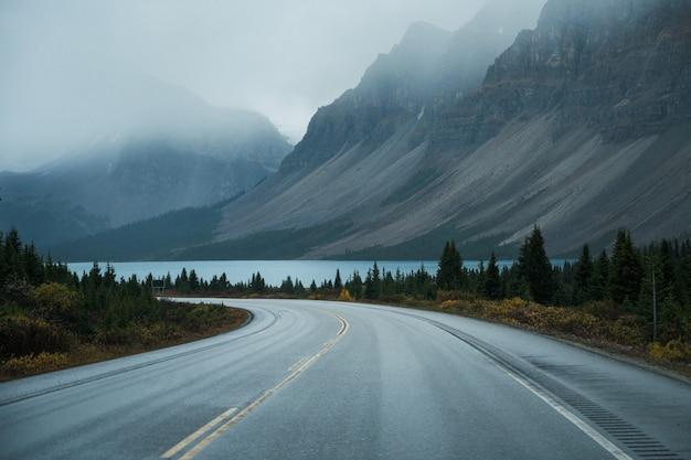 Viaje escénico con montañas rocosas y lago en un día sombrío