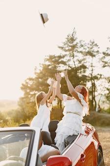 Viaje familiar feliz en coche por las montañas. gente divirtiéndose en cabriolet rojo. concepto de vacaciones de verano