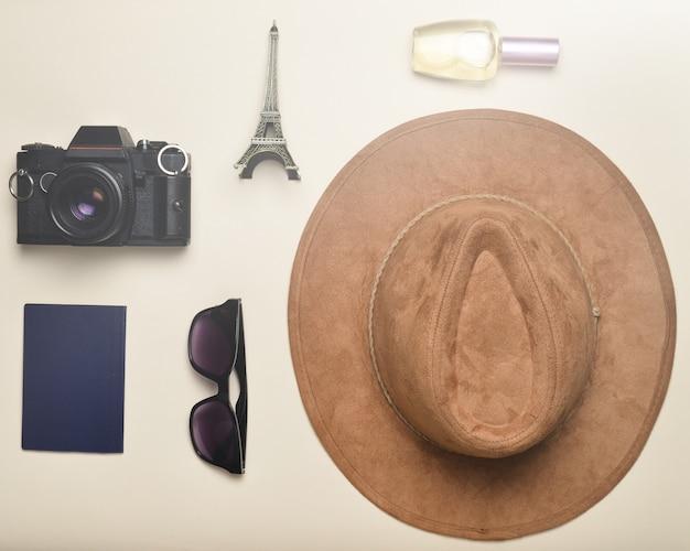 Viaje a francia, parís. sombrero de fieltro, cámara de cine, gafas de sol, pasaporte, frasco de perfume, estatuilla de recuerdo del diseño de la torre eiffel sobre un fondo de papel en colores pastel.