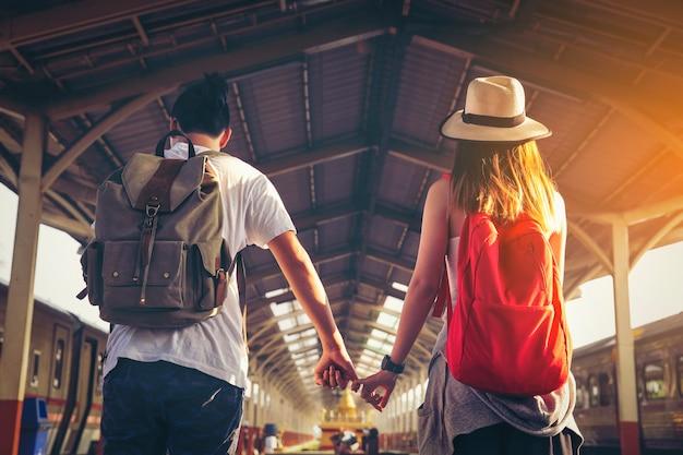 Viaje joven del turismo de la pareja en la estación de tren.