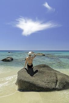 Viaje de lujo a cerdeña. mujer con sombrero en la playa en villasimius