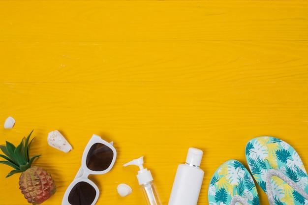 Viaje marino, cremas protectoras solares, zapatillas y piñas colocadas sobre un piso de madera amarilla.