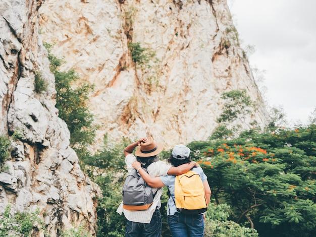 Viaje mayor de los pares en vacaciones de verano. ellos se dan la mano y caminan juntos.
