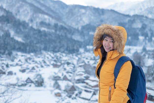 Viaje de la mujer en japón., retrato de invierno de joven bella mujer asiática en la nieve. concepto de moda de belleza de invierno que nieva en japón.