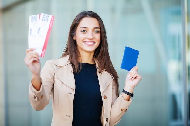 Viaje. mujer sosteniendo dos pasajes aéreos en el pasaporte extranjero cerca del aeropuerto