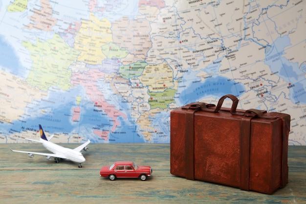 Viaje o viaje en concepto de avión. avión de juguete en miniatura y maletas en el mapa.