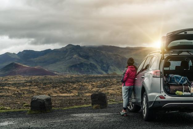 Viaje turístico de la mujer en coche suv en islandia.