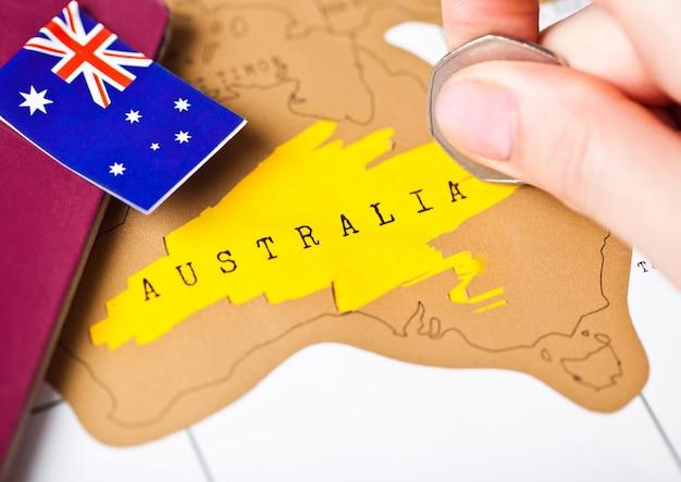 Viaje de vacaciones a australia concepto con pasaporte y bandera con mano femenina eligiendo australia en el mapa