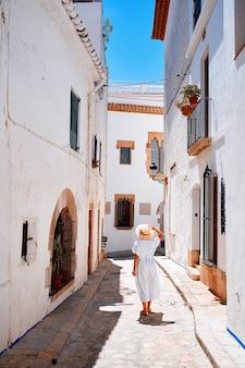 Un viaje de verano de mujer irreconocible. vista posterior de la mujer camina por las estrechas calles europeas. tiro al aire libre.