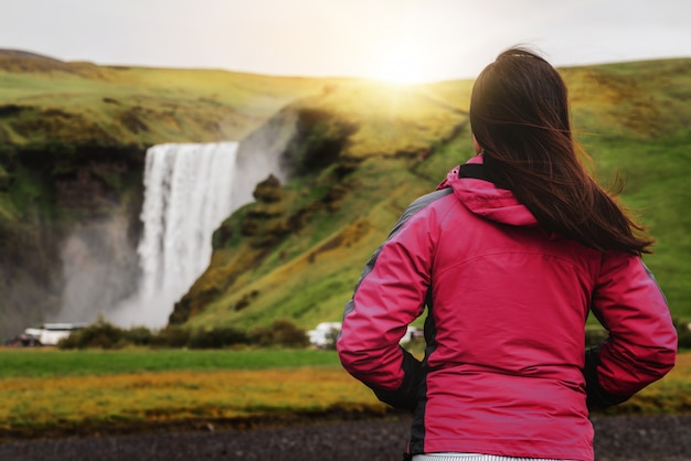Viaje del viajero a la cascada de skogafoss en islandia.